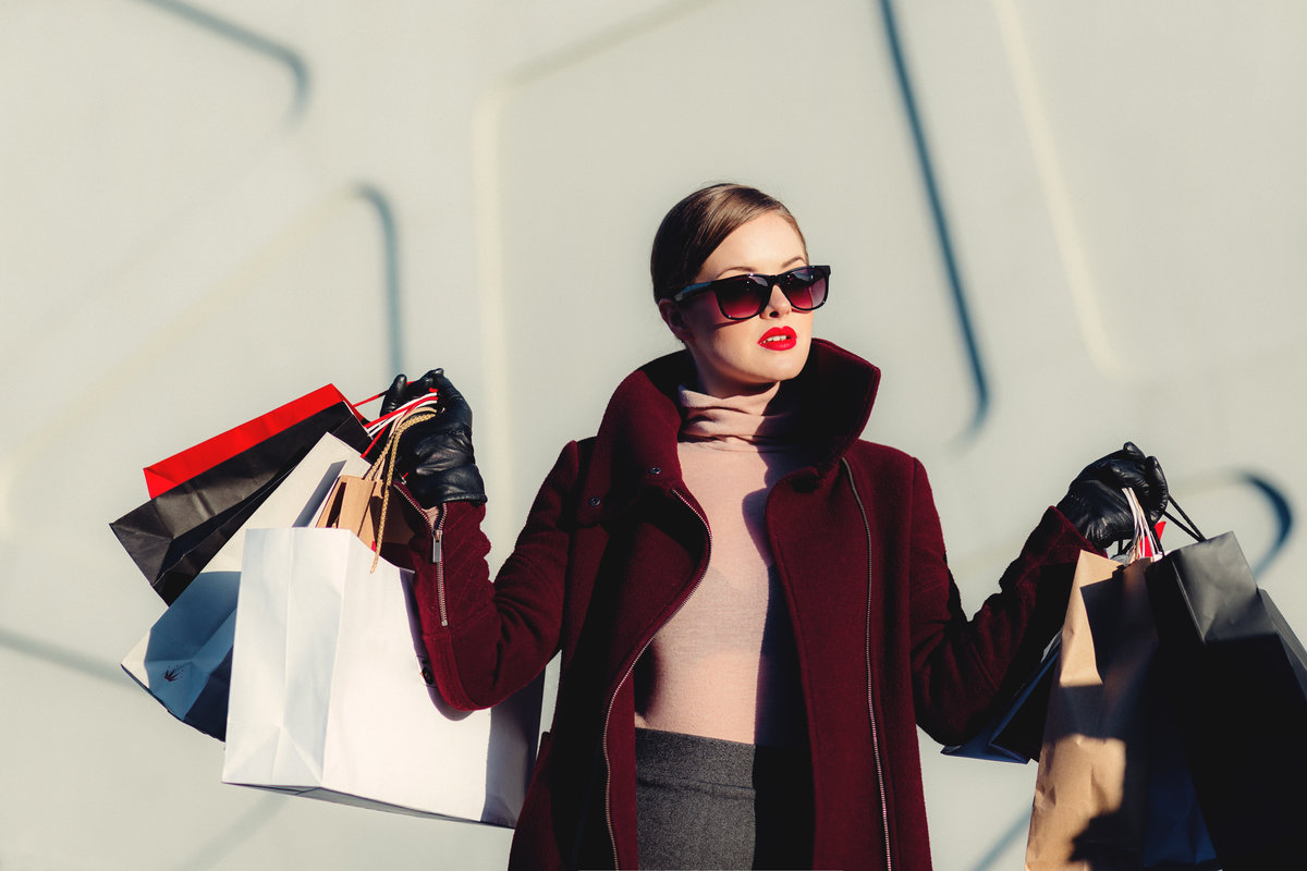 Fabulous young woman wearing big shades to hide her face. Very stylish and with many shopping bags in her hands